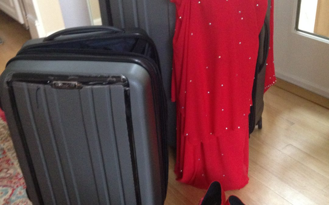 A suitcase, a red dress and a new pair of shoes